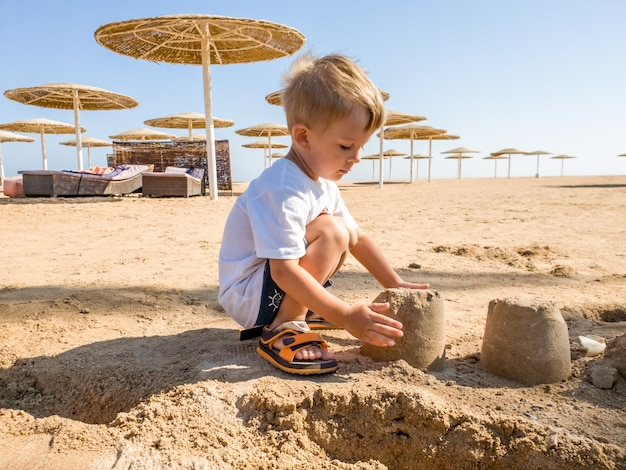 Portrait of adorable 3 years old toddler boy sitting on the sandy sea beach and building castle. child relaxing on summer holiday vacation