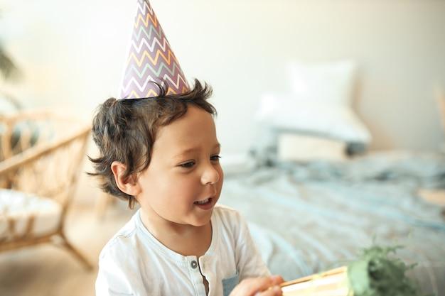 Ritratto di adorabile ragazzino di razza mista attiva con capelli ricci divertendosi al chiuso, in posa in camera da letto in cappello a cono