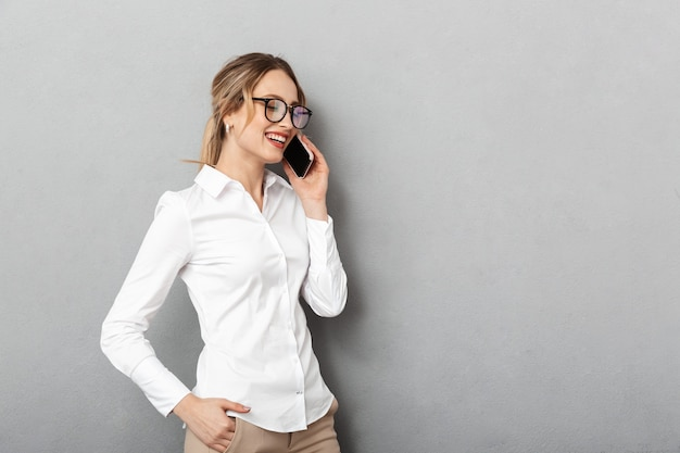 Portrait of adorable businesswoman wearing glasses smiling and speaking on mobile phone in the office, isolated