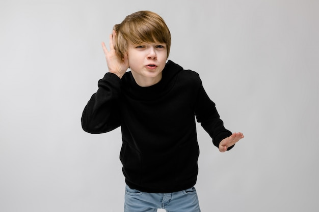 Portrait of adorable confident funny little boy standing in studio with hands near his ear listening