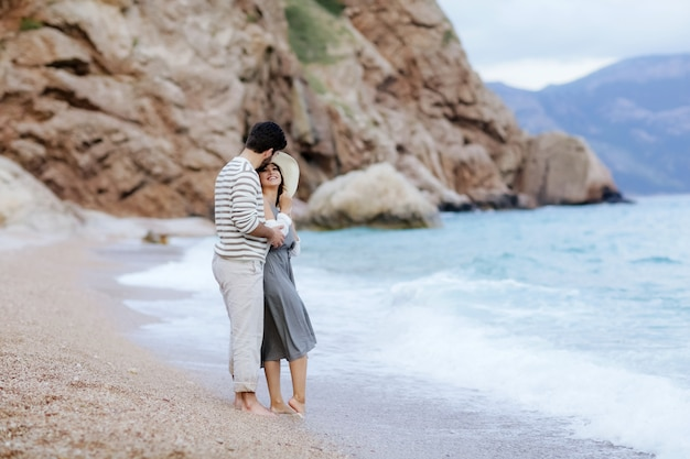 A portrait of an adorable couple in love kissing and embracing each other on the edge of the beach witj mountains at background
