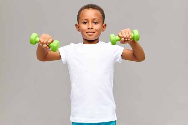 Portrait of adorable fit athletic dark skinned boy in white blank t-shirt doing morning physical exercise routine for biceps using two green dumbbells having energetic happy facial expression
