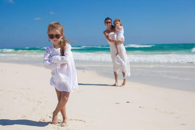 Portrait of adorable girl and her mother with little sister in the tropical beach