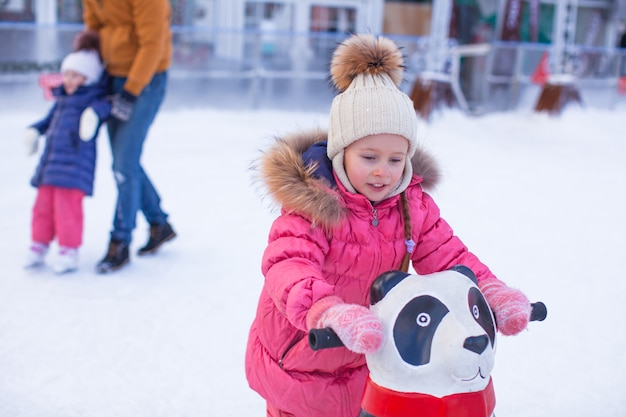 Portrait of adorable girl skating on the ice-rink background her father and little sister