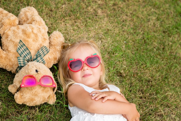 Portrait of adorable kid lying in beautiful green park with teddy bear in sunglasses.