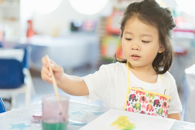 Portrait of adorable little asian girl holding a paintbrush and painting.