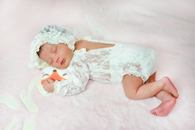 Portrait adorable of little asian newborn baby sleeping on fluffy soft bed.