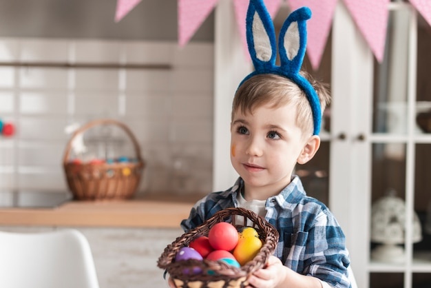 Portrait of adorable little boy holding a basket with eggs