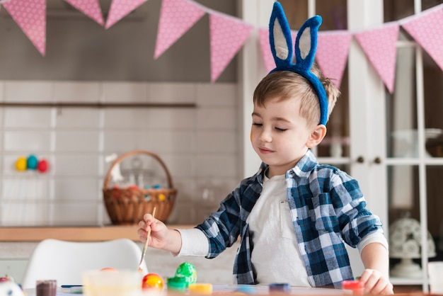 Portrait of adorable little boy painting eggs