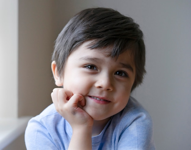 Portrait of adorable little boy sitting alone and looking at camera with smiling face