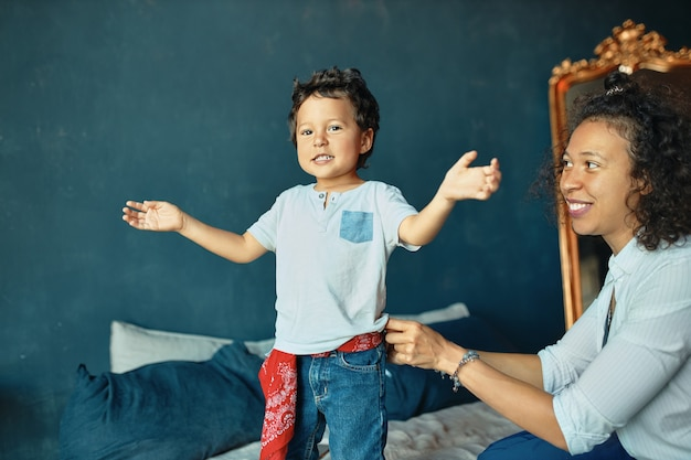 Portrait of adorable little boy with curly hair standing on bed, expressing positive emotions, young mother looking at son with pride and affection.
