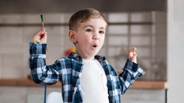 Portrait of adorable little child holding paint brush