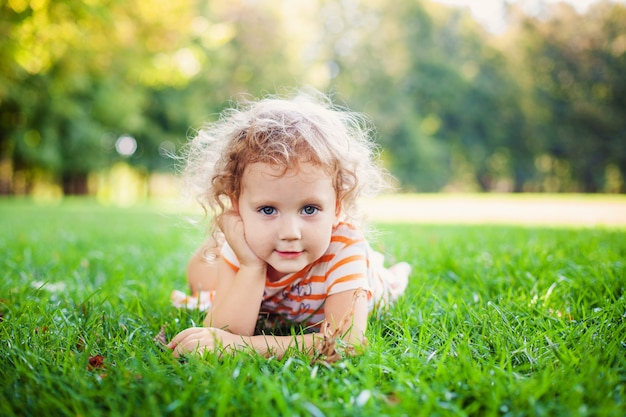 Portrait of adorable little curle girl lying on grass and propping up her face at summer green park