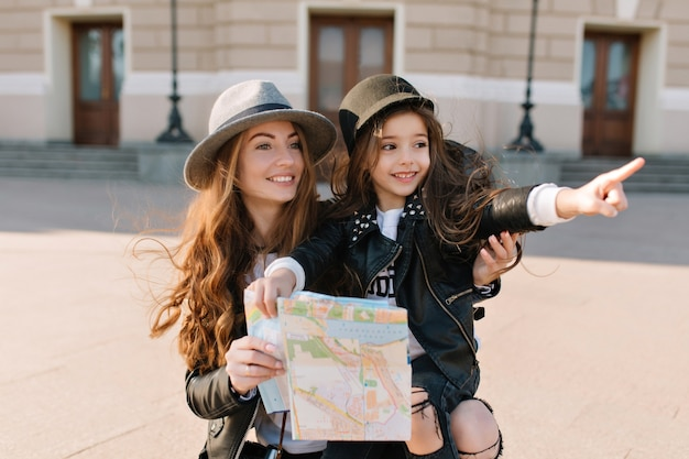 Portrait of adorable little girl in trendy hat pointing with finger at sights in new city during travel with mom. charming woman carrying cheerful daughter holding map and looking around with smile.