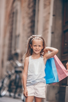 Portrait of adorable little girl walking with shopping bags outdoors in european city.