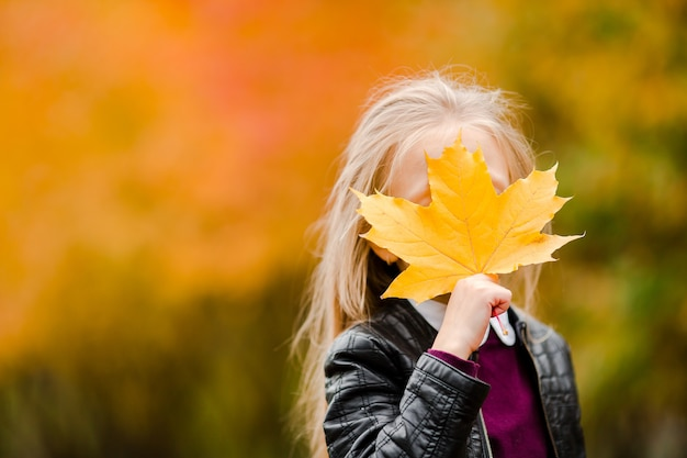 Portrait of adorable little girl with yellow leaves bouquet in fall on scooter