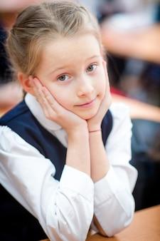Portrait of adorable little school girl in class