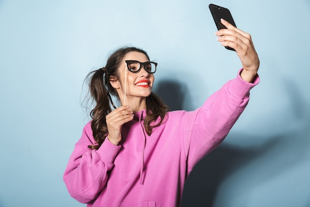 Portrait of adorable princess girl taking selfie photo on cellphone