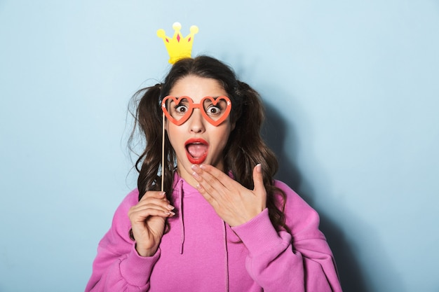 Portrait of adorable princess girl wearing paper crown laughing and holding funny sunglasses on stick over blue in studio