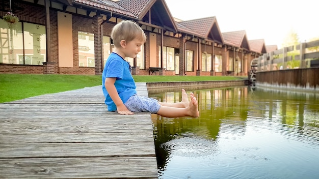 Portrait of adorable smiling toddler boy sitting at river in small town and holding feet in the water