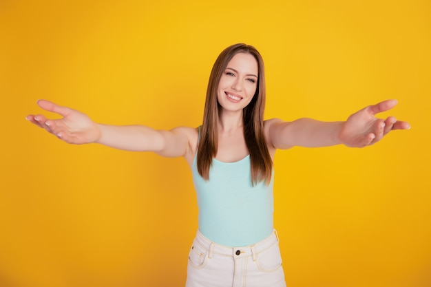 Portrait of adorable sweet nice welcoming lady stretch hands invite hug on yellow background