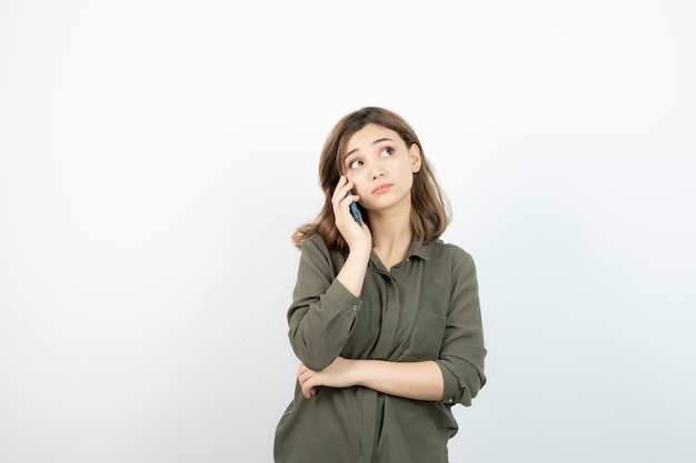 Portrait of adorable woman talking via cellphone over white.