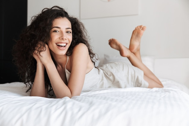 Portrait of adorable woman with long curly hair wearing silk leisure clothing lying in bed with white clean linen in apartment, and smiling