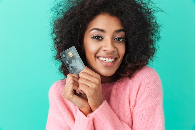 Portrait of adorable woman with shaggy hair holding plastic credit card and smiling sincerely, isolated over blue wall