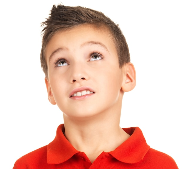 Ritratto di giovane ragazzo adorabile che osserva in su. isolato su bianco