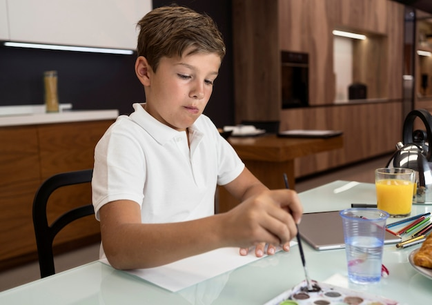 Portrait of adorable young boy painting