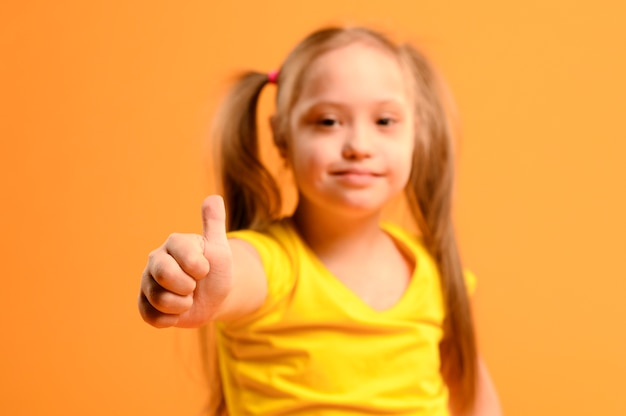 Portrait of adorable young girl with thumbs up