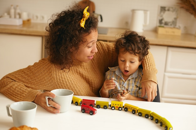 Portrait of adorably cute infant sitting on his mother lap holding glasses. happy mom having morning coffee in kitchen while son playing with railway set on table. parenthood and maternity leave