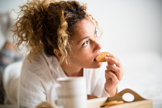 Portrait of adult beautiful woman eating cookie in morning breakfast in the bedroom