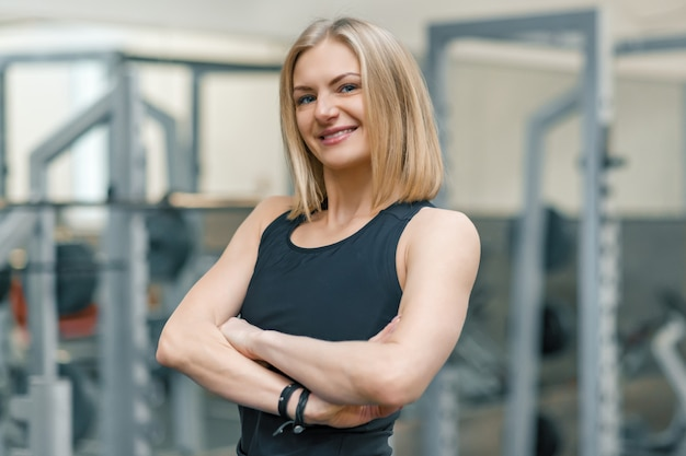 Portrait of adult blonde fitness woman personal trainer
