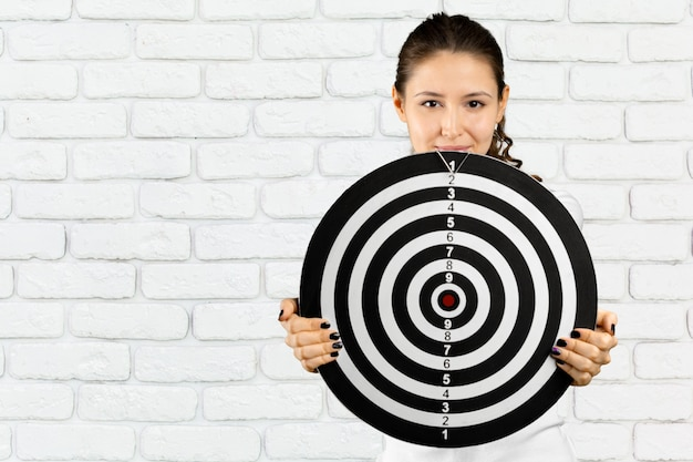 Portrait of adult blonde woman with board for darts