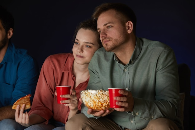 Portrait of adult couple watching movies at home while eating snacks and popcorn sitting on sofa in dark room