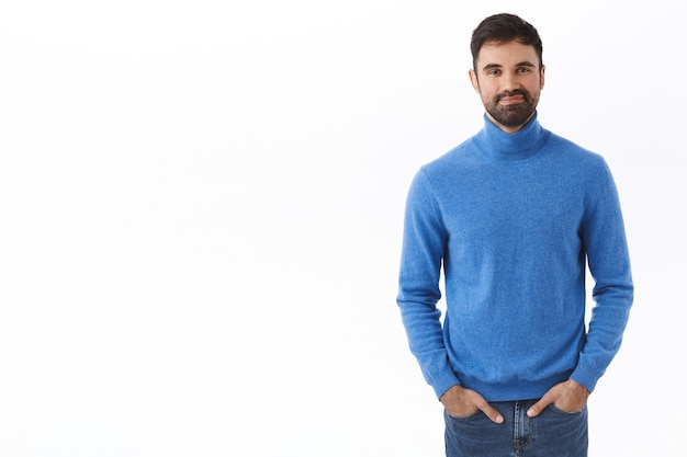 Portrait of adult handsome man with beard, hold hands in jeans pockets while smiling with friendly carefree expression, standing white wall casual normal pose