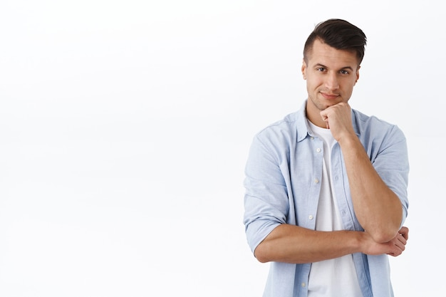 Portrait of adult handsome man with stylish haircut, casual outfit, smirk pleased, consider something, look  with satisfied face, making choice, thinking or pondering, white wall
