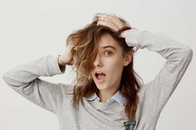 Portrait of adult lady with intriguing look touching her beautiful brown expressing surprise. fun and joy of woman 20s fooling around having mess with her hair. close-up