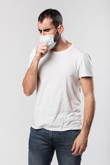 Portrait of adult male with face mask coughing