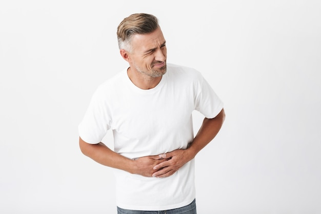 Portrait of adult man 30s with bristle wearing casual t-shirt touching his belly because of pain isolated on white
