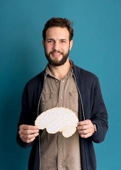 Portrait of adult man holding paper brain