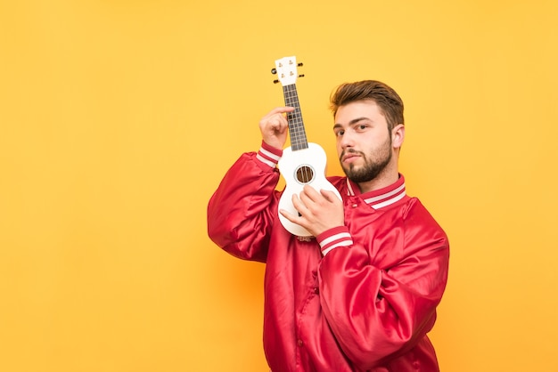 Portrait of an adult man standing with an ukulele in his hands on yellow and posing wearing a red jacket.