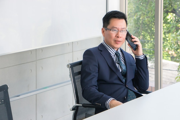 Portrait of an adult thai asian man wearing a suit, tie and glasses. he is sitting and talking on a cell phone in the meeting room at work in the morning.