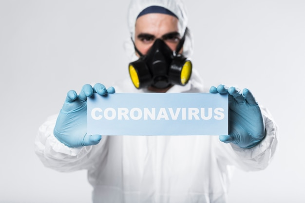 Portrait of adult with face mask holding coronavirus sign