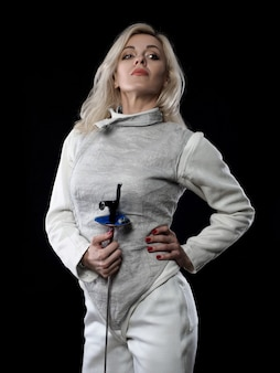 Portrait of adult woman fencer holding rapier. olympic sports, martial arts and professional training concept