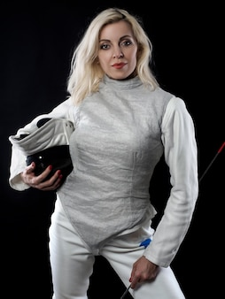 Portrait of adult woman fencer holding training mask and rapier. olympic sports, martial arts and professional training concept