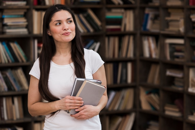 Portrait of adult woman holding books