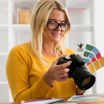 Portrait of adult woman holding professional camera