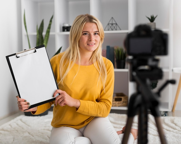 Portrait of adult woman recording video at home